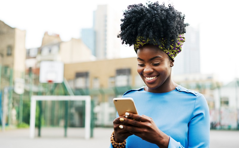 Woman smiling holding mobile phone